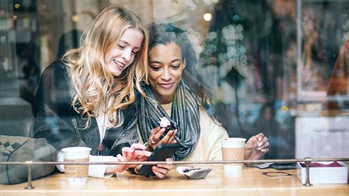 Zwei-Frauen-im-Cafe-mit-Smartphone